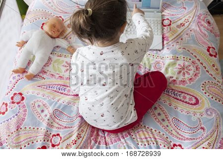 Little girl sitting in bed and playing online games with laptop computer. She is touching the screen
