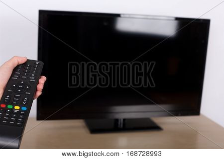 Hand using remote control turned off the TV