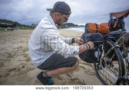 Long Distance Cyclist Prepares Panniers While On Beach