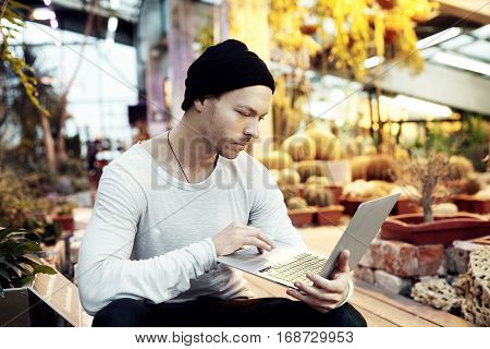 Handsome hipster man portrait working on start-up project on portable laptop computer. Guy in black hat looking ahead in a park sunny day. Business lifestyle concept