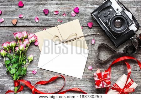 valentines day background. vintage retro camera with blank white greeting card and envelope with pink roses flower and gift boxes on rustic wooden background. top view