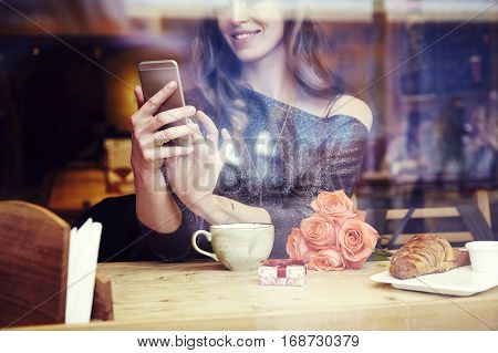 Young caucasian woman with long hair sitting near window in cafe or restaurant writing text message by phone smiling and looking at screen. Celebrating St. Valentine's day