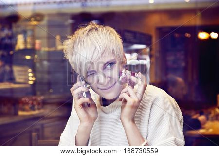 Blonde beautiful caucasian woman wearing white sweater sitting in cafe near window. Fanny face squints one eye wink. lady talking by mobile phone.