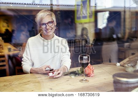 Beautiful blonde woman wearing eyeglasses looking to camera using mobile phone in cafe. Got a love message. Present box and rose flowers on wooden table. Romantique breakfast for a date or St. Valentine's Day.