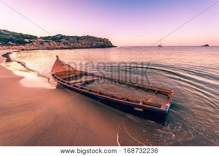 Old wooden boat wrecked on a sandy beach.