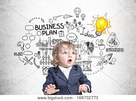 Portrait of a cute little boy in a suit sitting near a concrete wall with a business plan sketch and a glowing light bulb. Concept of business prodigy.