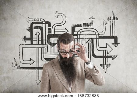 Portrait of a skeptical businessman with a long beard wearing glasses and a beige suit and standing near a concrete wall with a black tangled arrows sketch.