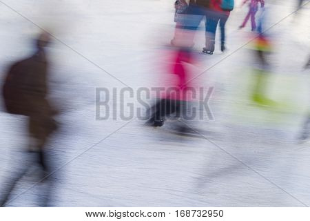 motion blur of different people skating on ice rink in the winter