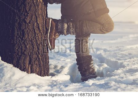 horizontal close up of woman wearing brown boots textile gaiters and blue jeans leaning against a large tree covered in snow in winter time concept for hiking