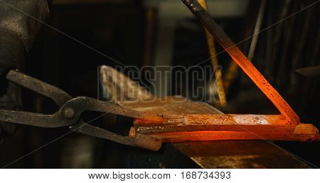 Rod hot iron on the anvil ready to be beaten.