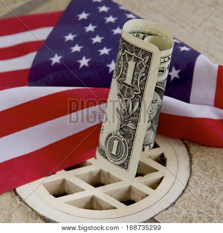 An American dollar going down the drain with a US flag in the background.
