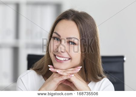Close Up Of Smiling Woman With Hands Under Chin