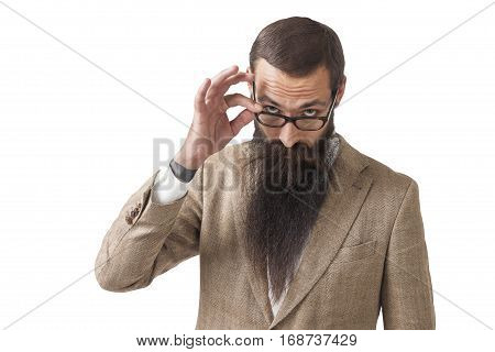 Isolated portrait of a businessman with a long beard wearing glasses and a beige suit and looking skeptically at someone off camera.