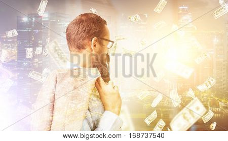 Side view of a bearded businessman in glasses holding his vest and standing under a dollar rain against a large skyscraper. Toned image. Double exposure. Mock up