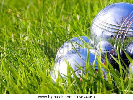 Bocce balls on a green grass. Close up with shallow dof.