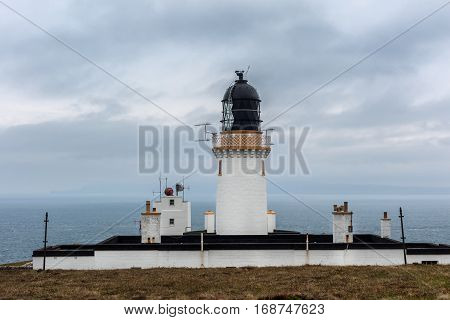 North Coast Scotland - June 6 2012: The lighthouse complex and tower at Dunnet Head against light blue sky. White towers with golden rim and black lighthouse cap with antennas. Set on brown grassy field.