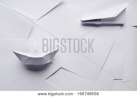 White paper planes and ship on a background sheet of office paper. Origami
