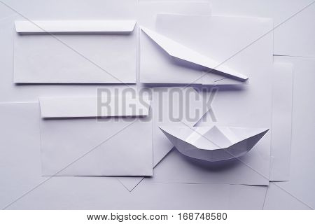 White paper envelope, planes and boat on a background sheet of office paper. Origami