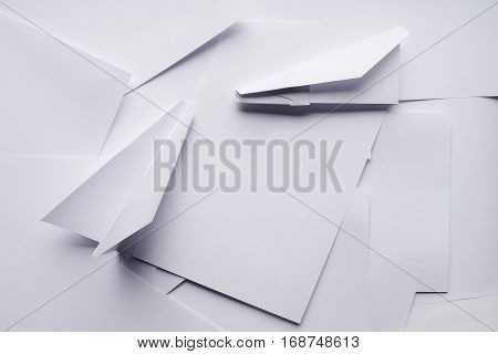 White paper planes on a background sheet of office paper. Origami