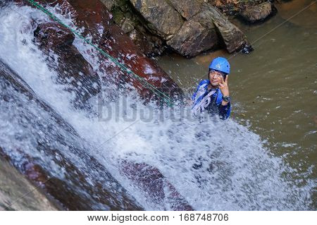 Beaufort,Sabah,Malaysia-Jan 28,2017:Happy adventure man rappelling Jempangah waterfall in Beaufort,Sabah,Borneo.Waterfall Abseiling activity adventure getting famous in Sabah,Borneo,Malaysia