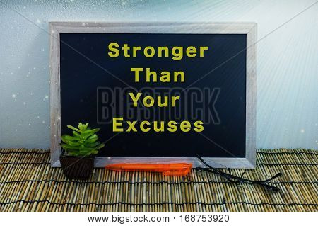 Business & creative concept-Stronger Than Your Excuses word on blackboard with green plant,pen & spectacle eyeglasses.