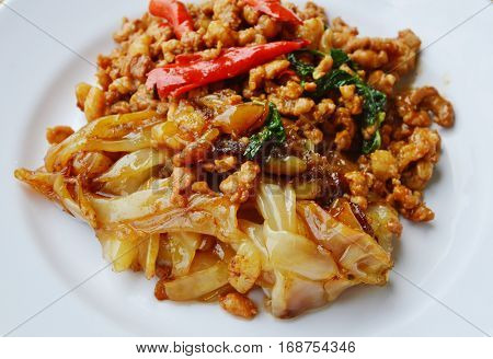 fried large noodle and spicy chop pork with basil leaf on dish