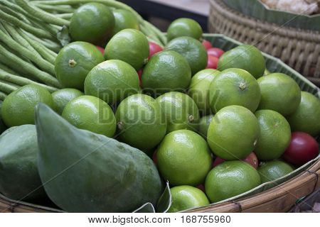 Green lime is a condiment that enhances the taste for Asian food sold at rural markets.