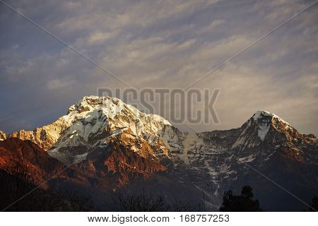 Amazing Landscape Of White Snow Capped Mountain Peaks And Craggy Hills Illuminated With Bright Sunsh