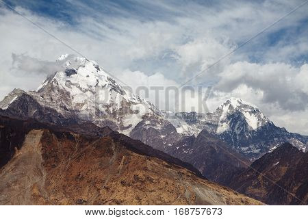 Morning Sky With Thick White Clouds Gathering Over Gigantic Snowy Summits And Craggy Cliffs. Amazing