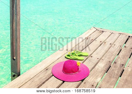 Large pink sun hat and green flip plops on the deck by the sea