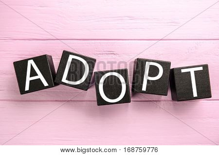 Black cubes with word ADOPT on color wooden background