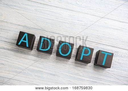 Black cubes with word ADOPT on light wooden background