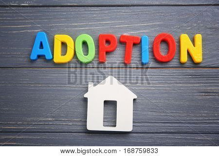 Word ADOPTION and figure in shape of house on color wooden background