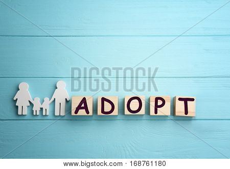 Cubes with word ADOPT and figure in shape of happy family on wooden background