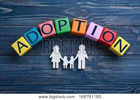 Cubes with word ADOPTION and figure in shape of family on wooden background