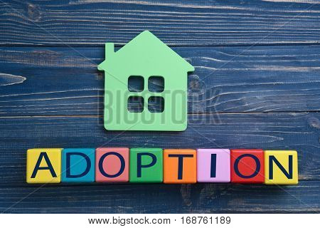 Cubes with word ADOPTION and figure in shape of house on wooden background