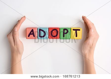 Female hands and colorful cubes with word ADOPT on white background