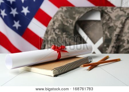 Notebook, diploma and pencils on white table. USA military education concept
