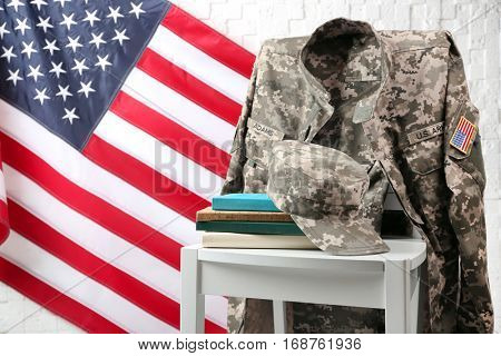 Chair, books, soldier uniform and USA flag near light textured wall. Military education concept