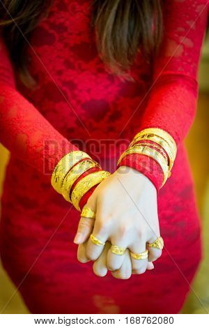 Chinese wedding gold jewelry on wrist and red dress