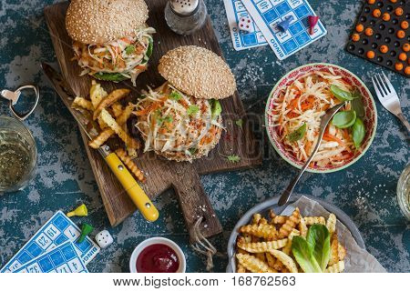 Hamburgers with grilled chicken and cole slaw on a wooden board on the table with cards and bingo chips top view. Flat lay
