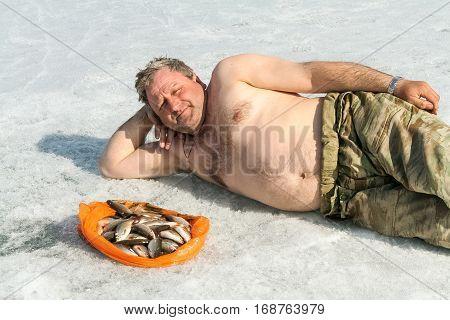 Man with fish on ice. Big lake, Siberia