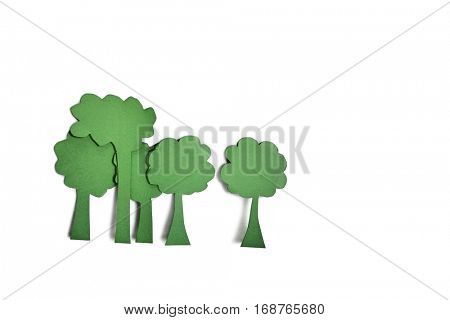 Paper cut outs of green trees over white background