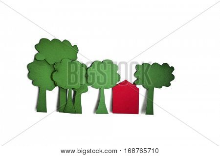 Paper cut outs of trees with a residential house over white background
