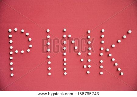 Close-up of push pins spelling pink over colored background