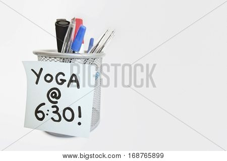Close-up of sticky note with yoga message on pen holder over white background
