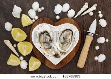 Oysters on crushed ice on a heart shaped plate on a maple wood board with oyster knife and pearls, lemon fruit and shells over old oak background. Top view.