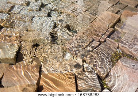 Cobblestone underneath of shallow water pool with reflective sunspots and light circles