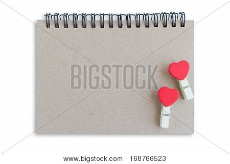 wooden clothespin with heart shape design and brown notebook for valentine concept isolate on white background