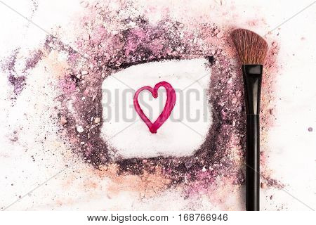 Makeup brush on white marble background, with traces of powder and blush forming a frame with a heart in it. Love Makeup valentine design